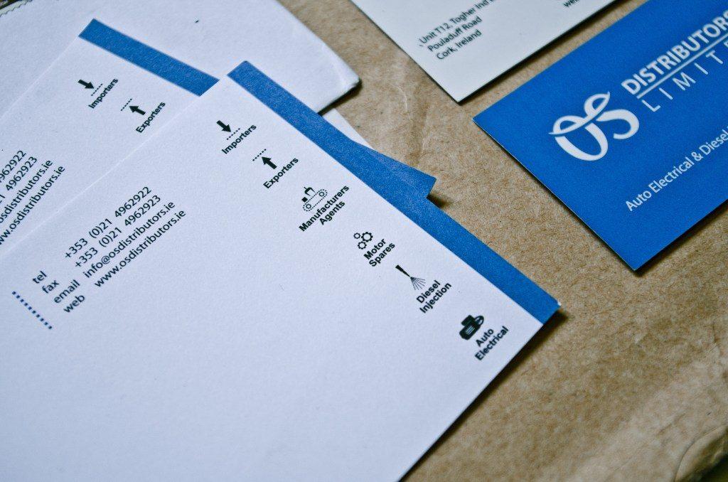 Na zdjęciu identyfikacja wizualna firmy OS Distibutors - wizytówki, koperta firmowa
