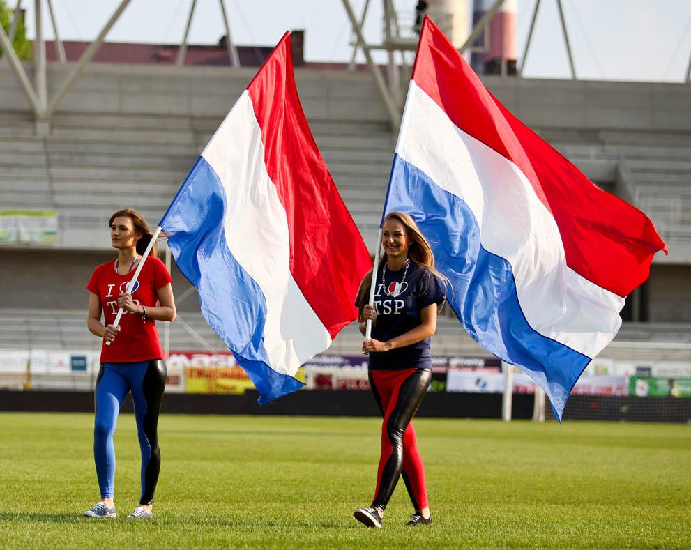 Stewardessy klubu TS Podbeskidzie w koszulkach klubu TS Podbeskidzie niosące flagi.